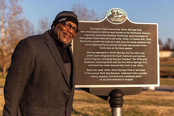 african american man standing next to a sign with historic information