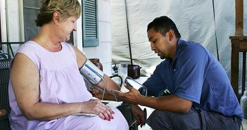 male hispanic health advocate checks a female resident's blood pressure on her porch