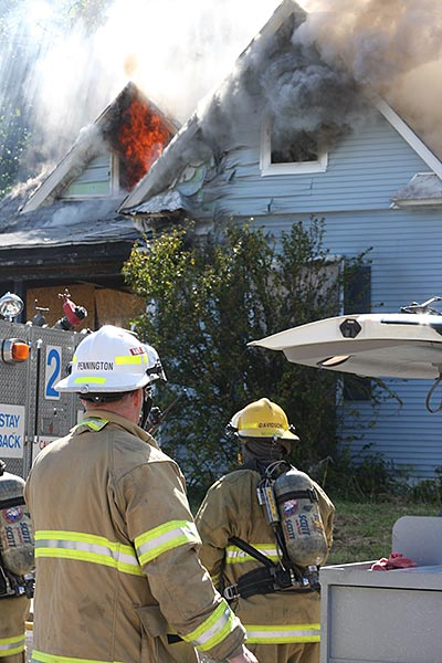two firefighters attending to a burning blue house